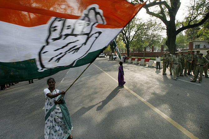 A supporter waves a Congress flag in front of the residence of Congress party chief Sonia Gandhi in New Delhi