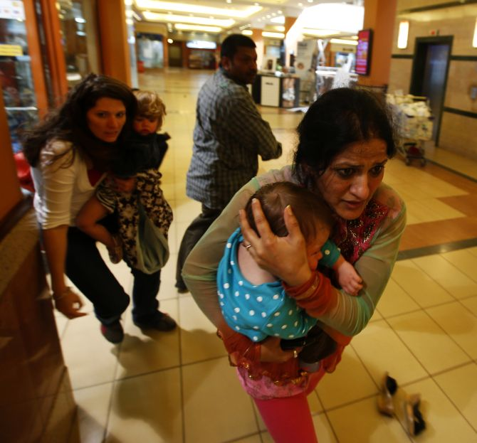 Women carrying children run for safety as armed police hunt gunmen who went on a shooting spree in Westgate shopping centre in Nairobi on Saturday.