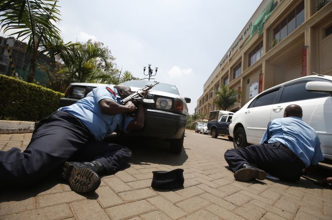 Police take cover outside Westgate shopping centre where gunmen went on a shooting spree in Nairobi