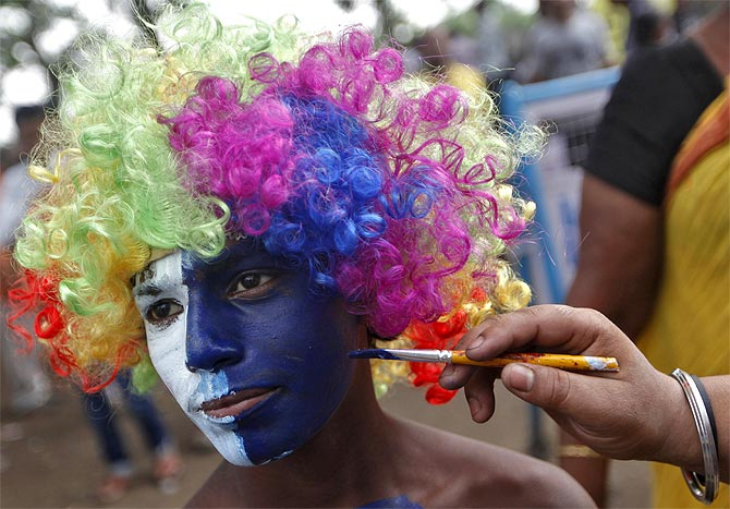 A cricket fan gets his face painted before an Indian Premier League game in Kolkata.
