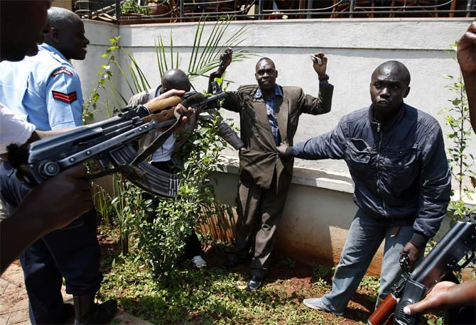 Policemen search a man for weapons as he walks out of Westgate Shopping Centre