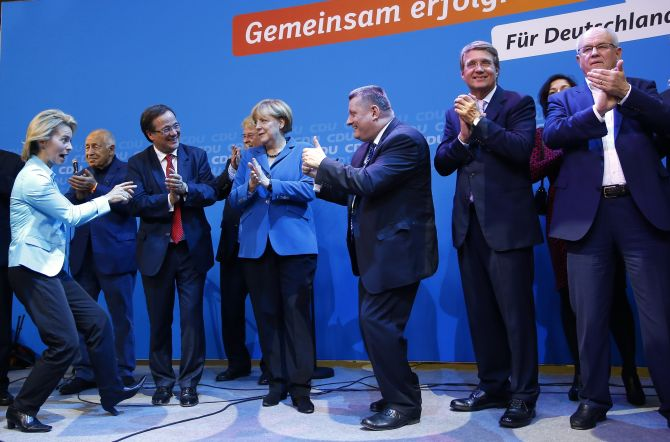 German Chancellor and leader of the Christian Democratic Union Angela Merkel (C) and CDU party fellows sing as they celebrate after first exit polls in the German general election at the CDU party headquarters in Berlin