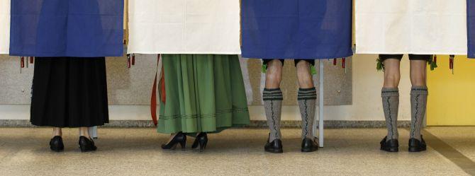 Voters Veronika Stuerzer, Monika Merk, Johann Merk and Michael Merk (L-R) wearing traditional Bavarian costume cast their ballots in the German general election