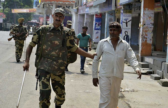 A jawan detains a person for questioning in curfew-hit Muzaffarnagar following communal clashes.