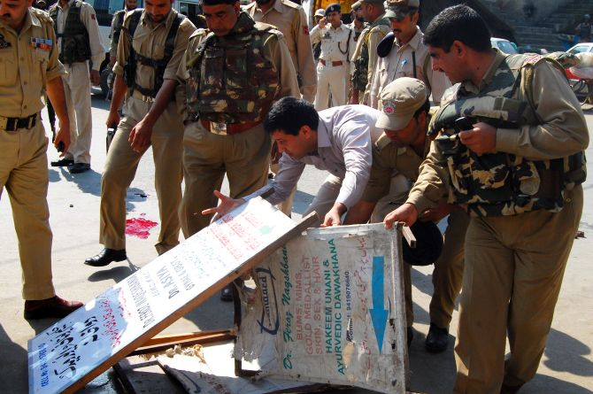 Senior police officers inspecting the site of a militant strike in the heart of Srinagar on Monday
