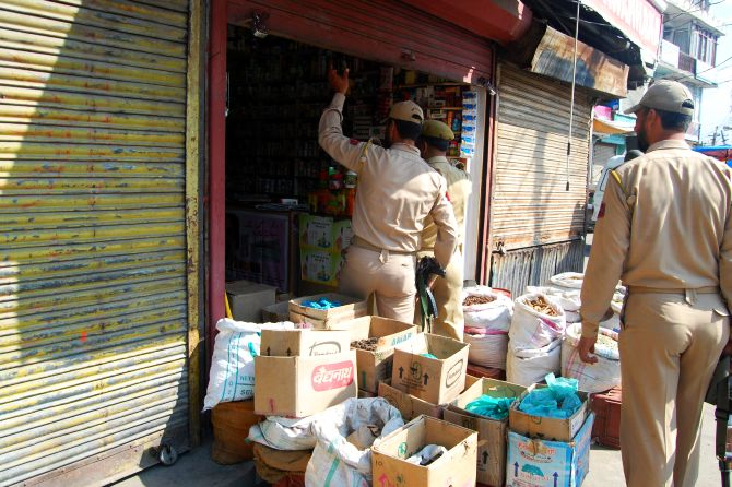 Kashmir Police personnel search shops near the site of the militant attack in Srinagar