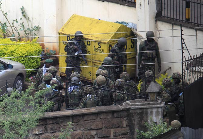Kenya defence forces soldiers take cover behind a wall