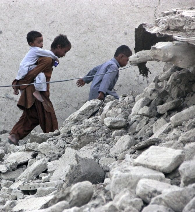 -Survivors of an earthquake walk on rubble of a mud house after it collapsed following the quake in the town of Awaran