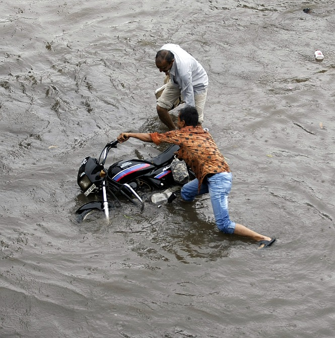 A man tries to right his motorcycle after it skidded in a flooded street after heavy rains in Ahmedabad