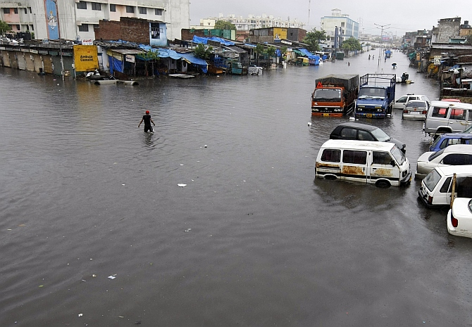 A man wades through a flooded street after heavy rains in Ahmedabad