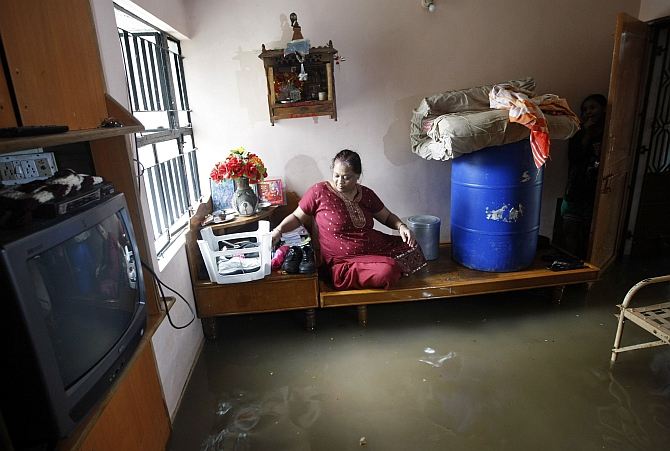 A woman sits on a bed inside her flooded room after heavy rains in Ahmedabad