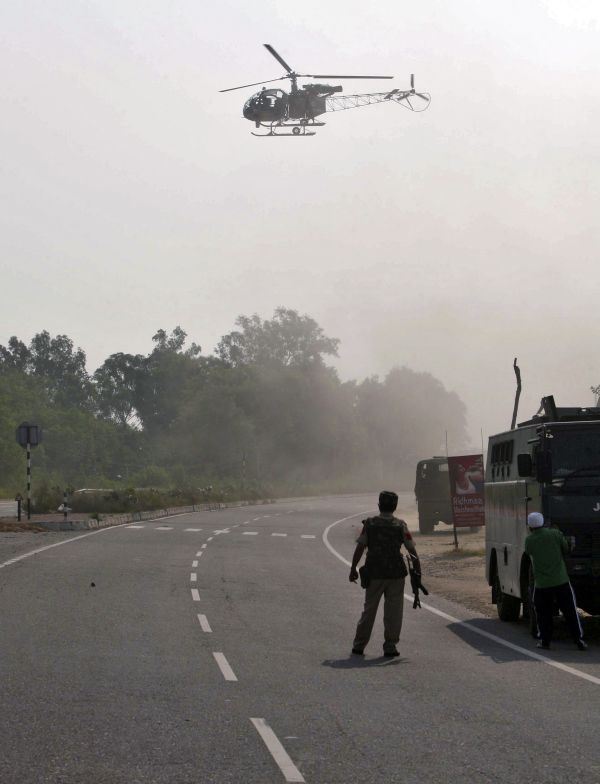An army helicopter hovers near an army camp during a gu