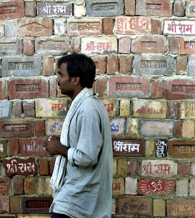 A Hindu activist walks past a temple wall, where devotees have written the name of Lord Ram, in Ayodhya