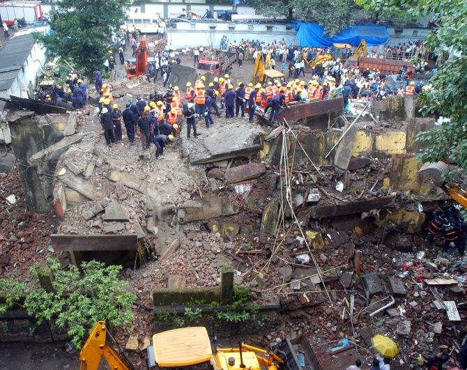 Firefighters and rescue personnel at the site of the building collapse in South Mumbai