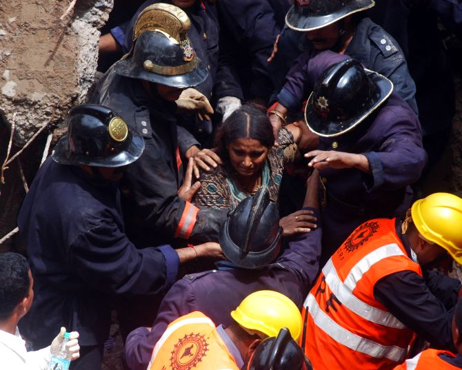 Firefighters rescue a trapped woman at the building collapse site in Mumbai