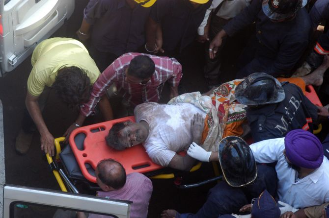 Firefighters rescue a man from the site of building collapse in south Mumbai