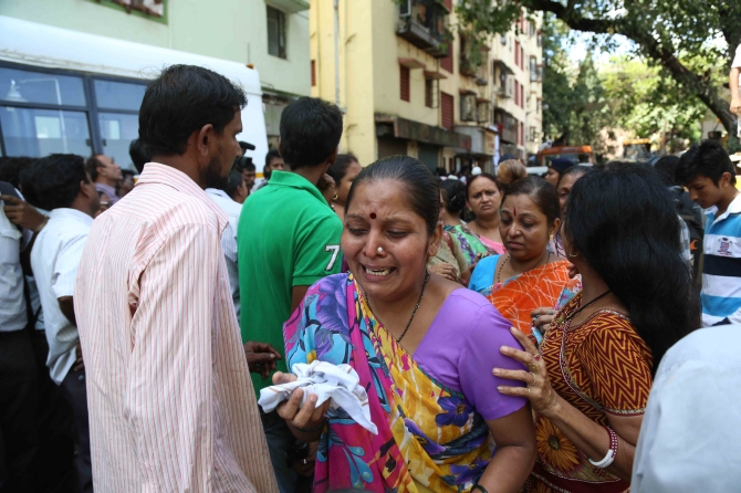 A family member of the person missing in the crash cries in Mumbai