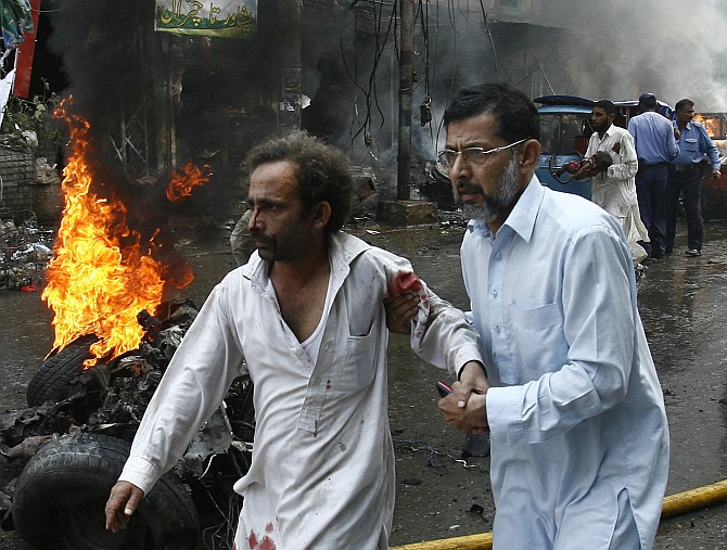A man helps an injured man walk away from the site of a bomb attack in Peshawar
