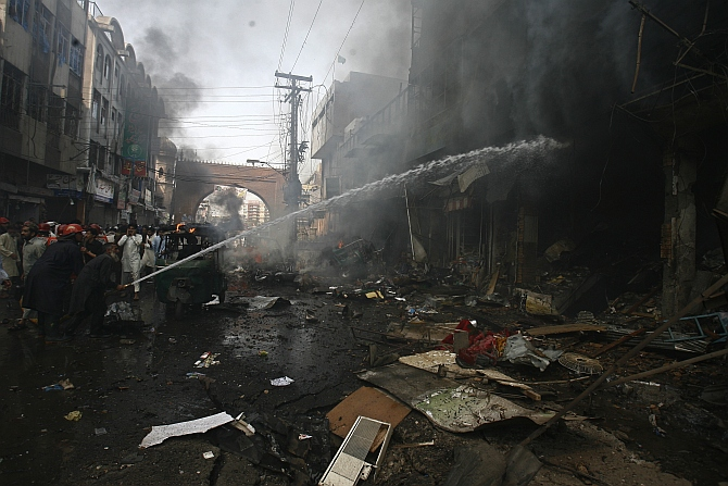 Firefighters extinguish a fire at the site of a bomb attack in Peshawar