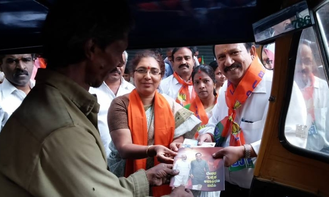 Tesajwini Ananth Kumar distributes pamphlets while campaigning for her husband.