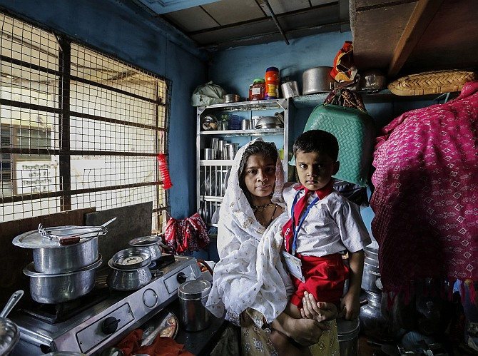 Nasreen Bano, a 22-year-old housewife, poses with her four-year-old son inside their one-room apartment in a residential building in Mumbai.