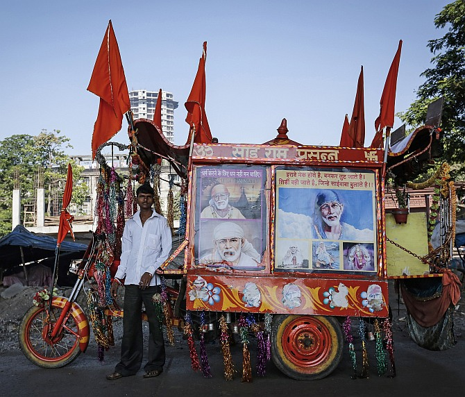 Suresh, 20, who runs a mobile temple, poses along a roadside in Mumbai
