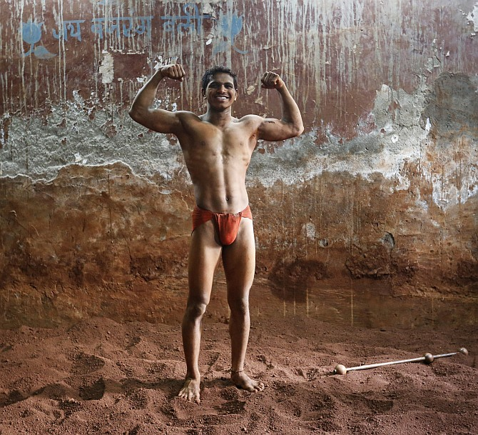 Deepak Mane, a 19-year-old wrestler, poses inside a traditional Indian wrestling centre called Akhaara in Mumbai.
