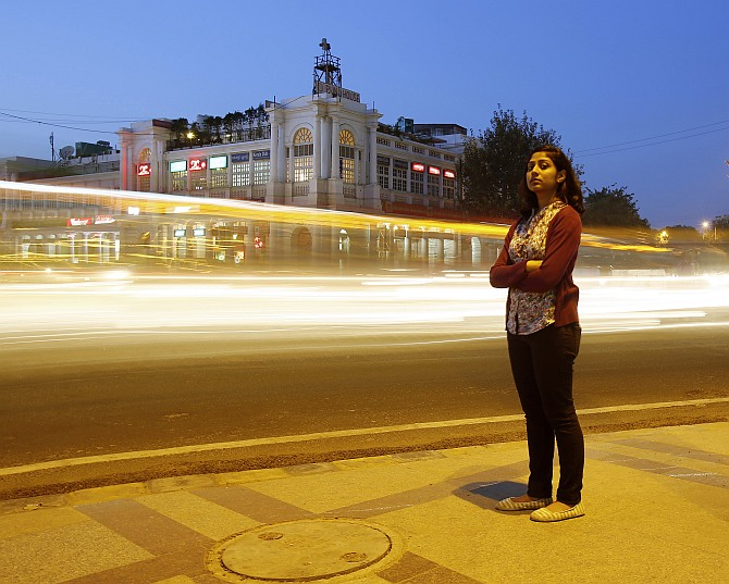 Inayat Naomi Ramdas, 21, poses for a photograph at a busy traffic intersection in New Delhi.