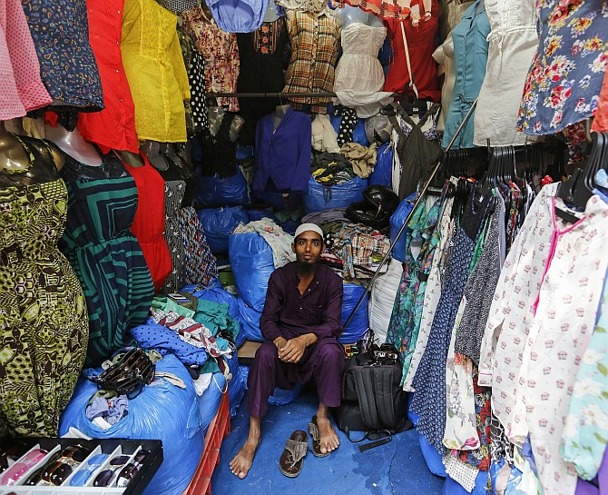 Mohammad Sabir, a 20-year-old salesman, poses inside his roadside shop at a market in Mumbai