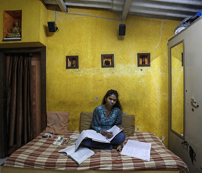 Riteesha Tambe, an 18-year-old college student, poses inside her house in Mumbai.