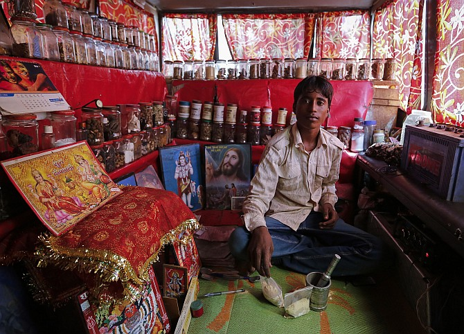 Shamsher Singh, a 19-year-old worker, poses inside a mobile traditional ayurvedic medicine shop in Mumbai.