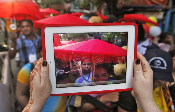 A participant uses a tablet to take pictures of a rally as part of the week-long sex workers' freedom festival at the Sonagachi red-light area in Kolkata.