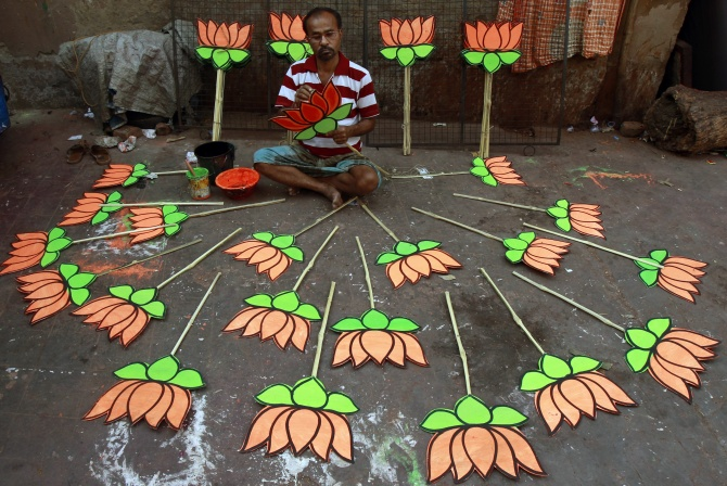 A worker paints a cut-out of a lotus at a workshop ahead of the election.