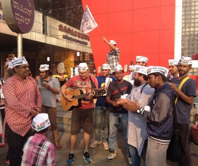 AAP volunteers play the guitar as Balakrishnan watches on during a campaign.