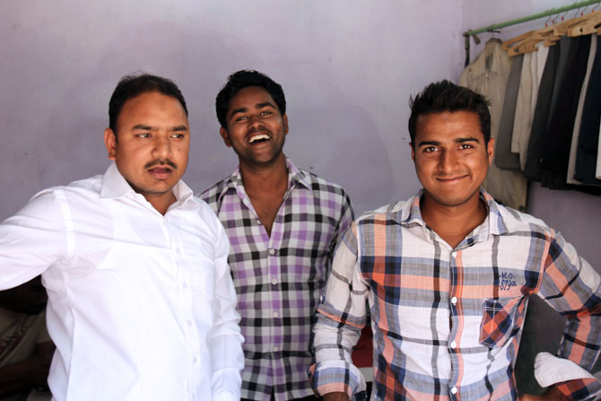 Raees Ansari, left, at his tailoring shop with Abrar Ahmed, a student, and Ansar Khan, an usher at a local multiplex.