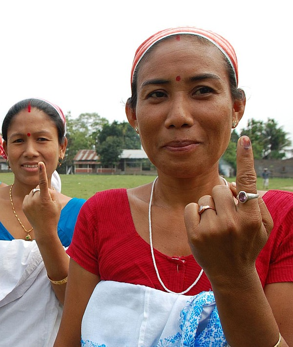 Women display indelible ink mark on their fingers after casting vote outside a polling station during the first phase of elections in Dibrugarh district of Assam