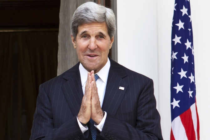 US Secretary of State John Kerry, on his first visit to India as secretary, makes a gesture of greeting to the media at the end of a photo opportunity in New Delhi.
