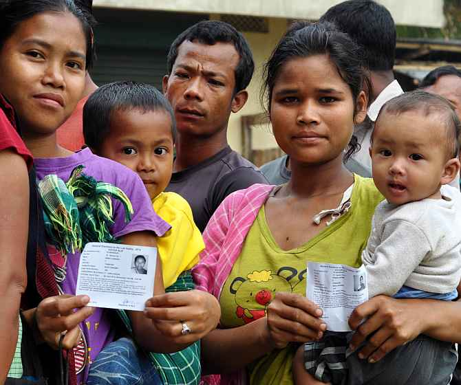 Voters flash their ID cards before casting their ballot at Harlibagan village near Shillong, Meghalaya, on Wednesday