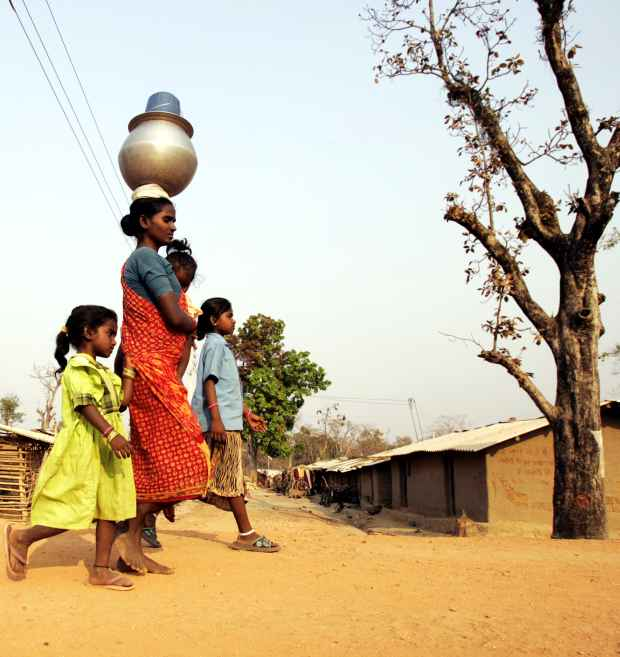 A mother with her kids returns home after fetching water in Maoist prone Bhairamgarh village in Chhattisgarh