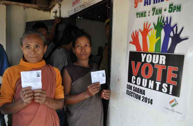 Voters flash their ID cards before casting their ballot in Meghalaya on Wednesday