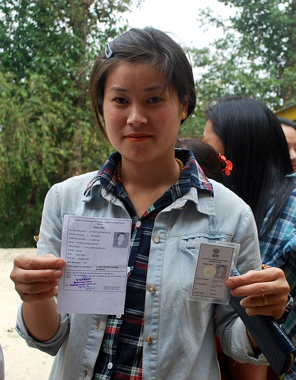 A first time female voter displaying her voter identity card at a polling booth in Sikkim