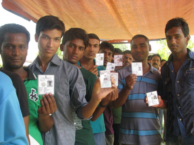 Young voters displaying their voter identity card at a polling booth in Tripura