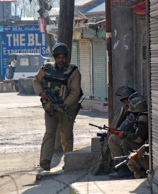 Security personnel take position where the terrorists were holed up.