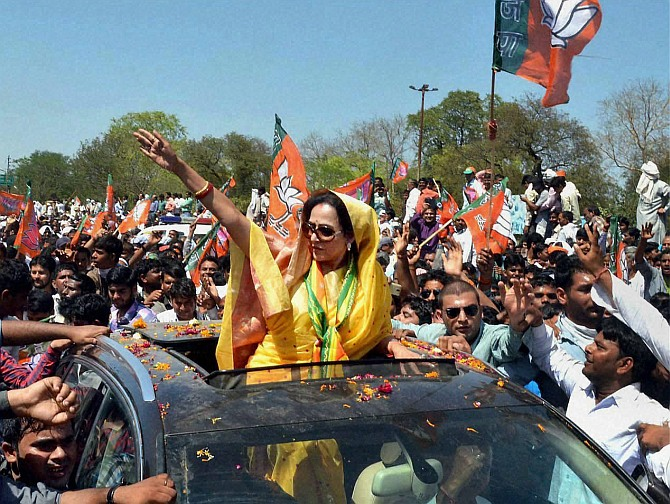 Actress and BJP candidate Hema Malni waves to supporters during her nomination filing procession in Mathura.