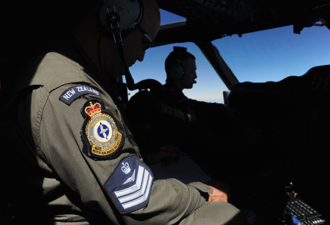 Pilot and captain Flight Lieutenant Timothy McAlevey (R), and flight engineer Chris Poole look from the cockpit of a Royal New Zealand Air Force (RNZAF) P-3K2 Orion aircraft, as they fly over the southern Indian Ocean to continue the search for missing Malaysian Airlines flight MH370