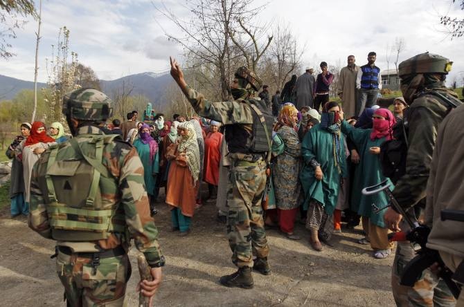 Indian soldiers with Kashmiris after a gunbattle with suspected terrorists at Khrew, south of Srinagar, April 13, 2014.