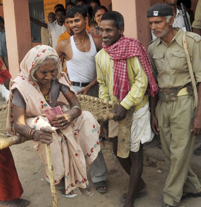 People help 80-year old Jashiya Devi to get to a polling station in Jehanabad in the eastern Indian state of Bihar