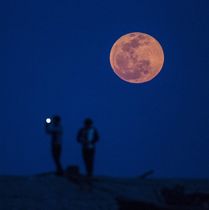 A man takes a picture during moon rise in a suburb of Shanghai