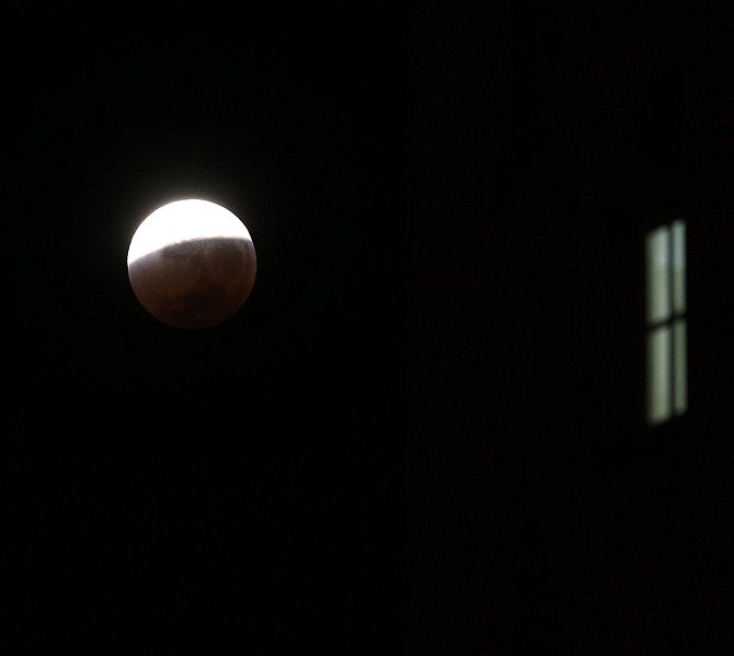 The moon is seen behind a building during a total lunar eclipse over Buenos Aires