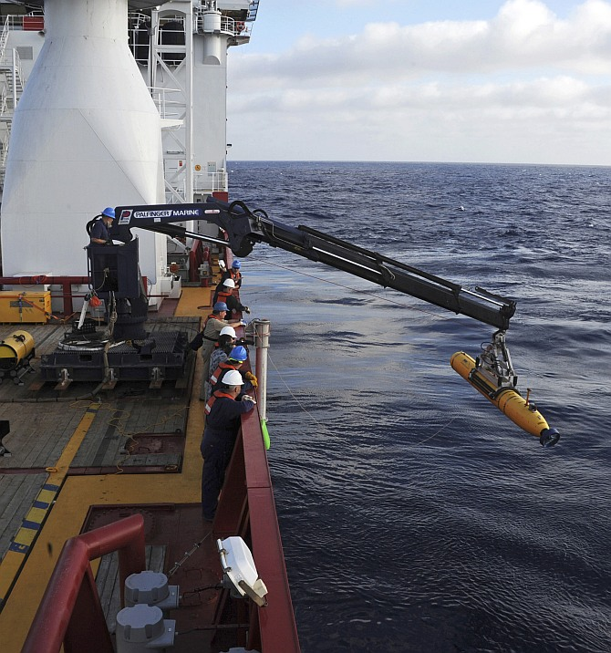 Operators aboard the Australian Defense Vessel Ocean Shield move the US Navy's Bluefin 21 autonomous underwater vehicle into position for deployment in the Southern Indian Ocean, as the search continues for the missing Malaysia Airlines Flight 370